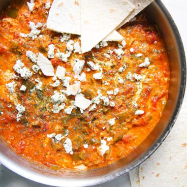 Menemen in a white pan with pita bread on the side