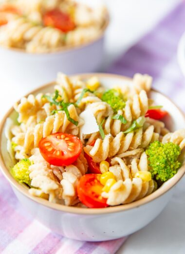 mediterranean hummus pasta salad in a bowl with tomatoes and broccoli on top